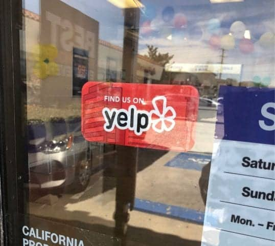 a find us on yelp sign in your shop window can increase your reviews